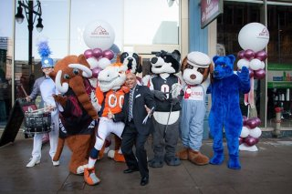 Denver Mayor Michael B. Hancock poses with associated with town's mascots before VISIT DENVER's recently established advanced Tourist Information Center.