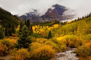 Maroon Bells concealed by autumn fog and autumn colors, near Aspen
